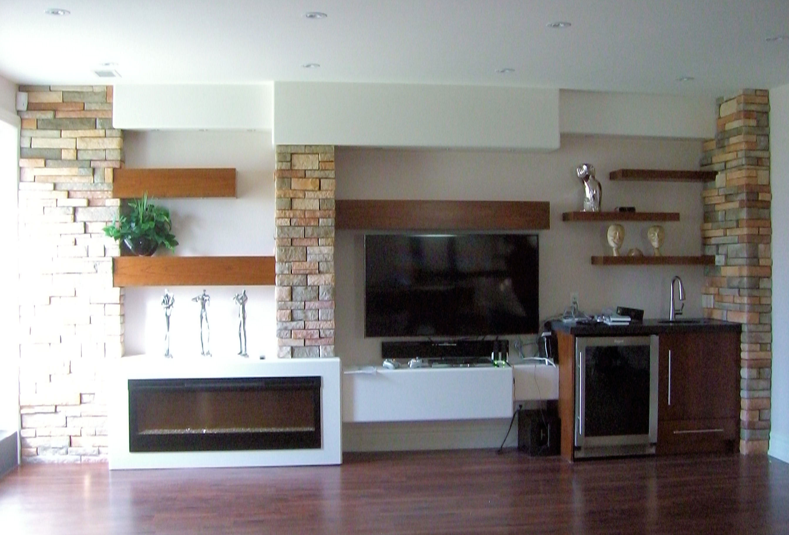 floating cherry wood shelves and beams set into a stone wall with ...