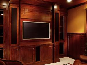 Art-and-Crafts Style Home Theater: The columns in this cherry wood home theater have roll-out trays and hold the tower speakers. The room is finished with solid raised-panel walls with fitted surround-sound speakers