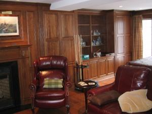 Wood Panelling extends to the window, floor-to-ceiling wall units provide storage and shelving
