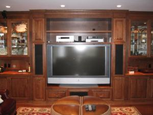 Glass displays surround a large built-in flat screen television. Designed for the discerning lifestyle