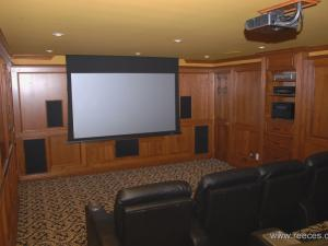 A stepped home theatre features a fixed TV and a large roll down screen. Custom Woodworking Elegant Living