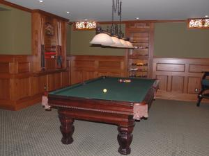 Custom renovation in pine - Here is a billiard room with custom pool cue stand. The heavy wood adds weight to the room for a distinctive look.