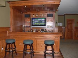 Reece's Custom Home Bar Design: This pub features a built-in TV screen, wine cooler and fridge. Wood panelling authenticates that pub feeling.