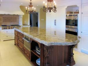 "Elaborate stained-cherry wood island with detailed corbels, 12' x 4', with custom-depth 2-1/4"" granite surface"