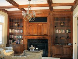 Floor-to-ceiling maple wall unit with TV insert and bi-fold doors.  Coffered Ceilings enhance the home entertainment unit.