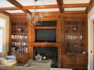 Floor-to-ceiling maple wall unit with TV insert and bi-fold doors