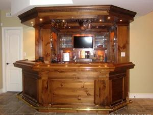 English Pub in knotty pine provides a warm welcome for friends. Note the brass foot rests--The full comfort of guests and homeowners is always considered in Reece's designs