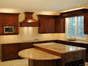 This cherry wood kitchen features half wand seating with height eat it counters in granite. There is a tile pattern with a distinct backsplash below a custom hood in cherry wood. The top window with light valence contains a platform lighting for convenient use