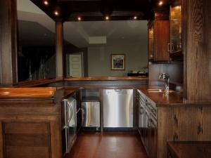 Dark oak bar with dishwasher, ice maker and fridge, ready for that big party. Reece's beautiful home bars are ideal for entertaining.
