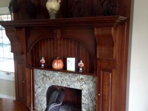 Reece's custom-designed & crafted fireplace in rich stain on cherry wood, granite hearth, featured in kitchen-dining area.