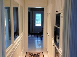 Butler's pantry in corridor area leading from kitchen, with mirrors set into panelling on one side creating the illusion of space