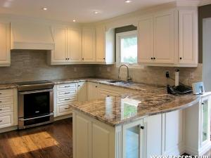 Painted custom cabinetry by Reece's, clean lines, stainless steel & polished granite