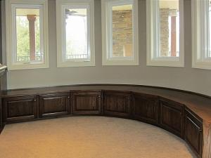 This large curved built-in window seat provides comfort for guests and adds remarkable beauty to this home renovation project