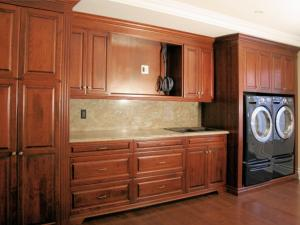 Custom cherrywood laundry coordinates with woodwork and custom cabinetry throughout this home,