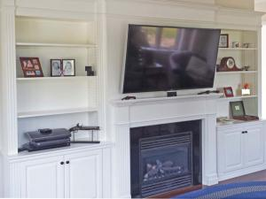 TV surface mounted above the fireplace & tilted towards the viewer