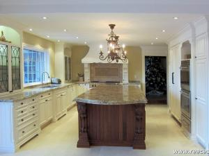 Traditional-style painted cabinetry with stained cherry wood island and built-in stainless steel appliances