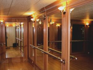 Note the elegant trim surrounding the mirrors, light sconces and brass railings.