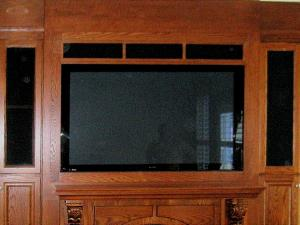 Oak stained and lacquer finished. Around the TV is a surround sound system built into the cabinet work