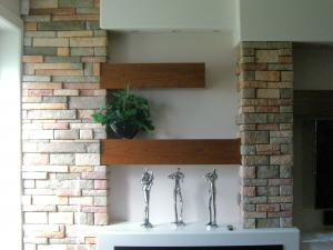 Contemporary design incorporates an electric fireplace, a home theater and bar area, featuring floating cherrywood shelves and beams set into a stone wall with painted bulkhead elements,