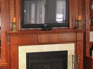 TV set into panel work above the fireplace. Warm golden brown finish