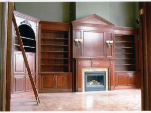 Fireplace mantel, wall unit and library custom-designed to suit 14' ceiling in this grand library. Cherry wood wall units grace this custom-designed home