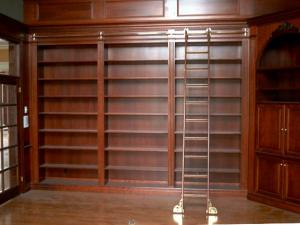 Cherry wood wall units grace this custom-designed library. Note the fine woodworking evident in the floor to ceiling shelving, panels, ladder, door trim