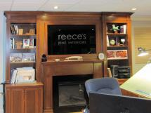 Cherrywood arts & crafts style wall units with TV over mantel on display in Reece's showroom