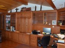 Home office in stained oak. There is a TV behind the pocket doors with storage for rolls of blueprints.