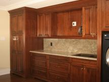 Luxurious cherrywood laundry room, custom built to include spaces for TV and built-in front-load washer & dryer