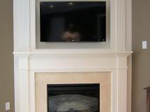 Clean lines and simplicity define modern styling in this fireplace mantel. Here is the perfect solution where you need a TV and a fireplace and space is at a premium. The clean lines of the wood surround provide elegance for this contemporary design