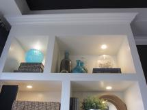Detail of contemporary wall unit shows led lighting fitted into shelves