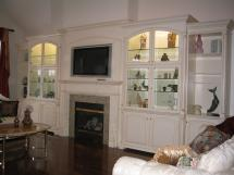 TV over Fireplace featured quarter turned & carved columns on wall units Featuring gold glazing on lacquered cabinets. Glass doors keep dust off of treasured collectables