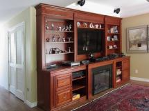 Classic wall unit in cherry wood, incorporating fireplace mantel, TV surround and storage